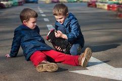 De tweelingbroers spelen met een stuk speelgoed auto Stock Fotografie