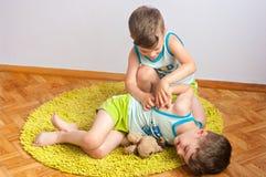 De tweelingbroers worstelen op de vloer Stock Foto