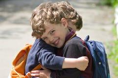 De tweelingen omhelzen elkaar aan omhelzing Stock Foto's