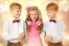 De tweelingjongens geeft een bloemenmeisje Valentine ` s en de kunstportret van de Vrouwendag Kind en jonge geitjesliefde Stock Foto's