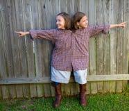 De tweelingmeisjes kleedden omhoog zich siamese met zijn vaderoverhemd royalty-vrije stock afbeeldingen