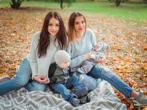 De tweelingmeisjes, zitten in een de herfstpark op een plaid, spelend met een kleine jongen en een baby royalty-vrije stock afbeelding