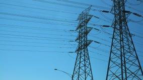 De tweelingtorens van de machtstransmissie op een zonnige dag stock afbeelding