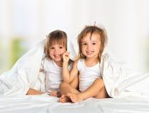 De tweelingzuster van het gelukkige meisje in bed onder de deken die hebben Stock Afbeeldingen