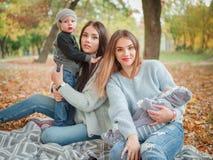 De tweelingzusters spelen met hun kinderen in het de herfstpark stock foto