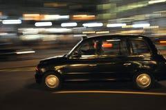 De typische taxi van Londen op de straten van het kapitaal van Engeland ` s Stock Foto