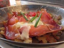 De typische Zuiden Tiroolse die schotel diende pan met vlek, bergkaas, eieren, aardappels en bieslook wordt gebraden stock afbeelding