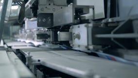De typografiemachine beweegt boeken op een transportband, geautomatiseerde productie stock footage