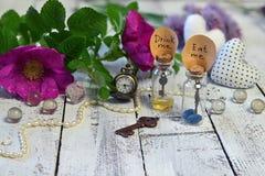 De uiterst kleine flessen met markeringen eten me en drinken me, klokken, zeer belangrijke en wilde rozen op planken Stock Foto