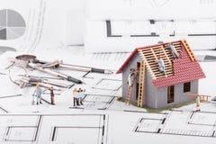 De uiterst kleine mensen bouwen huizen voor architecturale plannen Het concept van royalty-vrije stock afbeelding