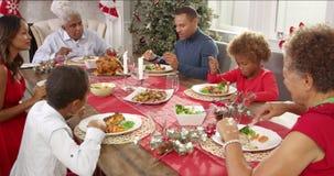 De uitgebreide zitting van de familiegroep rond lijst en samen het genieten van Kerstmis van maaltijd stock video