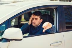 De uitgeputte jonge mensenzitting achter het stuurwiel van de onderzoeksauto die duim onderaan gebaar tonen ontbrak de bestuurder stock foto's
