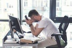 De uitgeputte rijpe werknemer zit bij bureau stock foto's