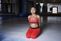 De uitgeputte zwetende Aziatische vrouw in sport kleedt zich ademhaling en het uitrekken na harde opleidingsfitness training stock afbeelding