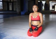 De uitgeputte zwetende Aziatische vrouw in sport kleedt zich ademhaling en het uitrekken na harde opleidingsfitness training stock foto