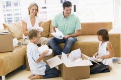 De uitpakkende dozen van de familie in het nieuwe huis glimlachen Royalty-vrije Stock Afbeelding
