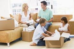 De uitpakkende dozen van de familie in het nieuwe huis glimlachen Stock Foto's