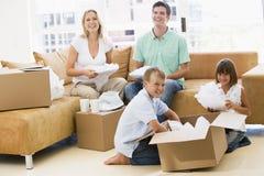 De uitpakkende dozen van de familie in het nieuwe huis glimlachen Royalty-vrije Stock Foto's