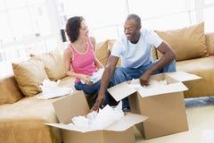 De uitpakkende dozen van het paar in nieuw huis stock foto