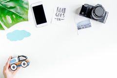 De uitrusting van het kinderentoerisme met camera en mobiel op witte vlakte als achtergrond legt model Stock Foto