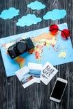 De uitrusting van het kinderentoerisme met mobiel, de kaart en de beelden op donkere vlakte als achtergrond leggen model Royalty-vrije Stock Foto's