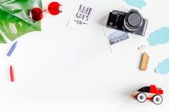 De uitrusting van het kinderentoerisme met speelgoed en de camera op witte vlakte als achtergrond leggen model royalty-vrije stock foto