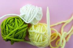 De uitstekende Breinaalden en het garen op een roze achtergrond, een GLB bonden met witte natuurlijke wol Met het onduidelijke be Stock Foto's