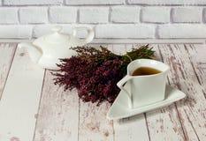 De uitstekende ceramische witte kop en de theepot op witte houten achtergrond met heide, sluiten omhoog stock foto