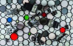 De uitstekende de filmcamera's en flitsen liggen op een achtergrond van multi-colored glas fotografische filters van diverse groo royalty-vrije stock foto's