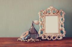 De uitstekende flessen van het antigueparfum met oude omlijsting, op houten lijst retro gefiltreerd beeld Stock Fotografie