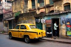 De uitstekende gele taxiauto hield bij de oude straat op Stock Foto