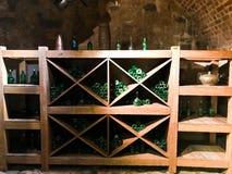 De uitstekende groene lege wijn en bierglasflessen in een wijnkast met planken in oude middeleeuws bricked steenkelder stock afbeeldingen