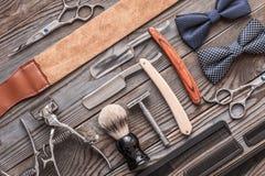 De uitstekende hulpmiddelen van de kapperswinkel op houten achtergrond stock afbeelding