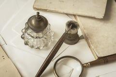 De uitstekende kantoorbehoeften, de houten pen, de inktpot, meer magnifier en de enveloppen, brieven sluiten omhoog Het schrijven royalty-vrije stock foto