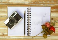 De uitstekende oude camera met boek en potlood op houten Royalty-vrije Stock Afbeeldingen