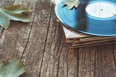 De uitstekende oude vinylverslagen op houten de herfstachtergrond, selectieve nadruk verfraaiden met weinig bladeren Muziek, mani Stock Foto's