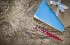 De uitstekende pen van blocnotes rode biro op houten raad stock foto