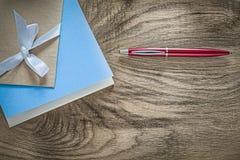 De uitstekende pen van blocnotes rode biro op houten raads hoogste mening stock foto