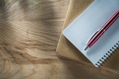 De uitstekende pen van blocnotesbiro op houten raad royalty-vrije stock afbeelding
