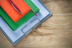 De uitstekende pen van klembordblocnotes op houten raad royalty-vrije stock foto