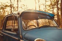 de uitstekende retro blauwe kleur van autovolkswagen in Forest Leaves Brown Royalty-vrije Stock Afbeelding