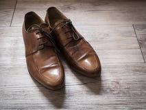 De uitstekende retro schoenen van het mensen bruine leer op een houten vloer Stock Foto