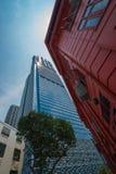 De uitstekende rode bouw met houten blinden en moderne skysraper Royalty-vrije Stock Foto