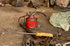 De uitstekende Rode Smeerolie kan met Vettige Hulpmiddelen op Vuile Concrete Grond royalty-vrije stock afbeelding