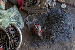 De uitstekende Rode Smeerolie kan met Vettige Hulpmiddelen op Vuile Concrete Grond - Herstellend Eqipment stock afbeeldingen