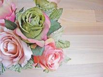 De uitstekende rozen over houten lijst sluiten omhoog stock afbeelding