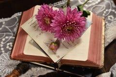 De uitstekende stijlvlakte legt foto met geopende boek en bloemen royalty-vrije stock afbeelding