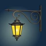 De uitstekende straat hangende lamp, die met geel licht tegen de avondhemel gloeien, met een gietijzermuur zet op Royalty-vrije Stock Fotografie