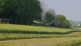 De uitstekende Trein van de Stoommotor en Personenauto's die in Amish-Platteland aankomen stock videobeelden