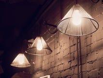De uitstekende verlichtingslamp hangt voor cementbakstenen muur bij zolder royalty-vrije stock foto's
